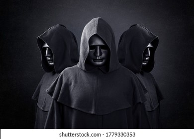 Group of three scary figures in hooded cloaks in the dark