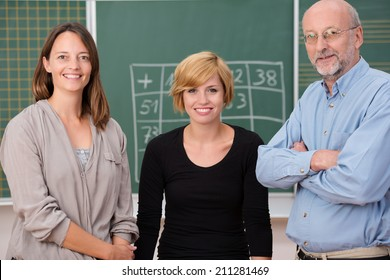 Group of three school teachers with confident friendly smiles standing in front of a class blackboard, one man and two women