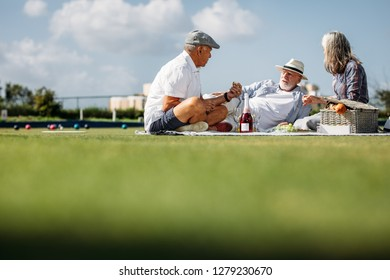 Group of three senior friends sitting in a park enjoying food and drinks. Two senior men and a woman eating snacks during a break at the boules park.
