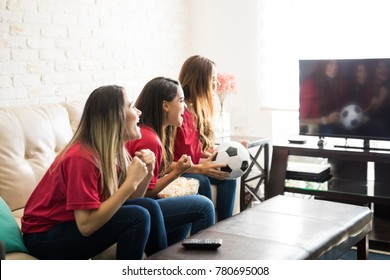 Group of three soccer fans watching a game on tv and looking excited after their team scored a goal
