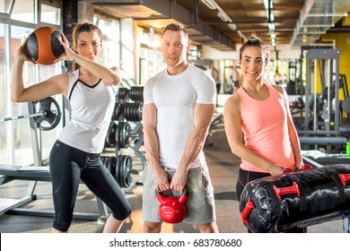 Group of three sporty people posing with exercise equipment in gym.