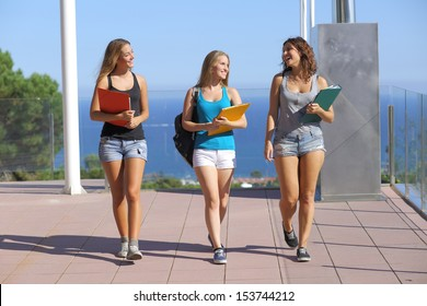 Group of three student teenagers walking towards camera with the sky in the background
