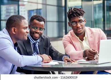 A group of three stylish African American students entrepreneurs in fashion business suits working sitting at table with laptop in a summer cafe outdoors
