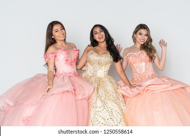 Group of three teenage hispanic girls wearing quinceanera dresses