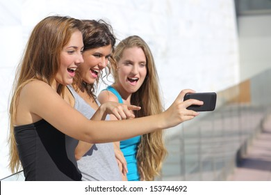 Group of three teenager girls amazed watching the smart phone outdoor