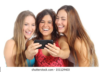 Group of three teenager girls laughing looking the smart phone isolated on a white background