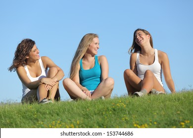 Group of three teenager girls laughing and talking on the grass with the sky in the background