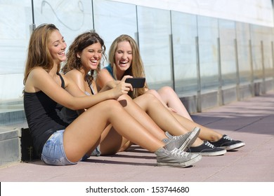 Group of three teenager girls sitting on the floor laughing while watching the smart phone
