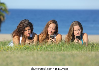 Group of three teenager girls typing on the mobile phone lying on the grass with the sea in the background