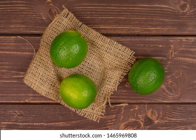 Group of three whole fresh green lime on a natural sackcloth flatlay on brown wood