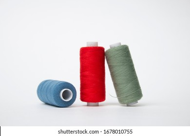 Group of Three whole haberdashery item colorful thread spools isolated on white background. Coloured threads. Colorful bobbin thread.