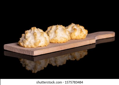 Group of three whole homemade golden coconut biscuit on small wooden cutting board isolated on black glass