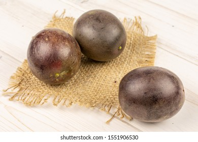 Group of three whole sweet dark purple passion fruit on natural sackcloth on white wood