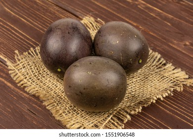 Group of three whole sweet dark purple passion fruit on natural sackcloth on brown wood
