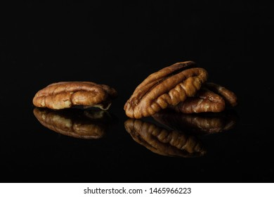 Group of three whole unshelled fresh brown pecan nut half isolated on black glass