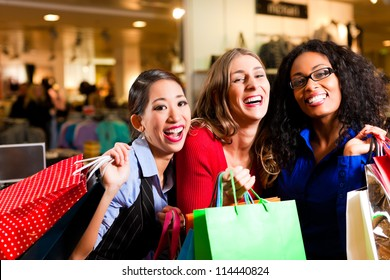 Group of three women - Caucasian, Latina and Asian - shopping downtown in a mall