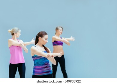 Group of three women stretching in fitness studio - fitness, sport, training, gym and lifestyle concept.