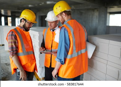 Group of three workmen wearing protective helmets and vests standing among concrete walls on construction site discussing development progress with foreman inspector