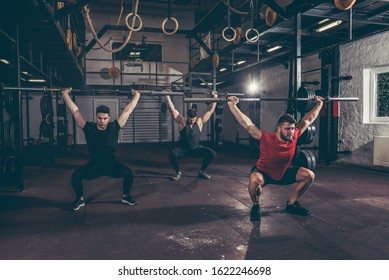 Group of three young friends fit muscular fitness guys having fun by hard core cross workout training in the gym with barbells and squats selective focus