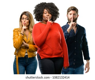 Group of three young men and women with index finger on lips, ask to be quiet. Silence and secret concept