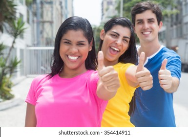 Group of three young people in colorful shirts standing in line and showing thumbs