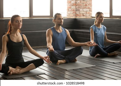 Group of three young sporty people practicing yoga lesson with instructor, sitting in Sukhasana exercise with eyes closed, Easy Seat pose, mudra gesture, working out, indoor close up, studio