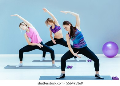 Group of three  young women doing stretching exercise in studio.