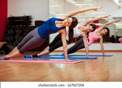 Group of three young women practicing the side plank pose during yoga class in a gym