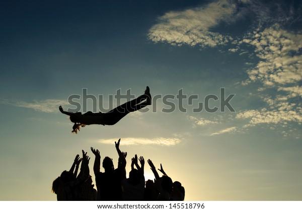 Gruppe, die Mädchen in die Luft wirft