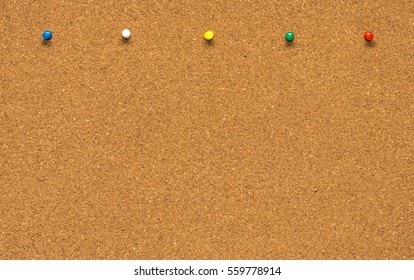The Group of thumbtacks pinned on corkboard