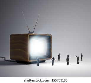Group of tiny people watching a TV program in vintage television set