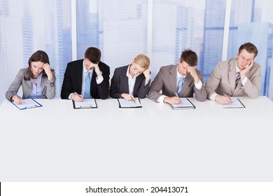 Group of tired corporate personnel officers at table in office
