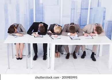 Group of tired corporate personnel officers sleeping at table in office