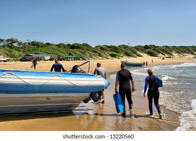 Group of tired scuba divers passes by boat. Shot in Sodwana Bay, KwaZulu-Natal province, Southern Mozambique area, South Africa.
