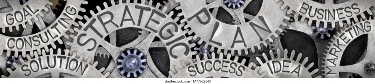 Group of tooth wheels with Strategic Plan, Business, Success, Idea and Goal concept related words imprinted on metal surface