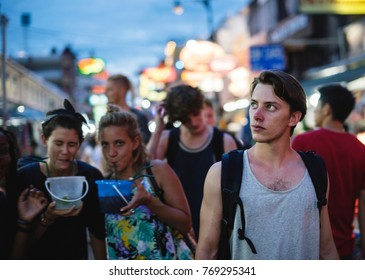 A group of tourist enjoying bucket drinks in Khao San Road, Bangkok, Thailand