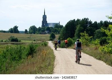 Group of tourist riding bicycles by dirty road in countryside,group cyclists on a way between fields,cyclists touring in Lithuania, by bicycle in Lithuania countryside, cycling bicycle on dirty road