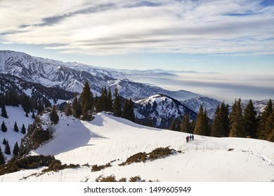 Group of tourist are walking down the snow path at beautiful cloudy sky background. Outdoor climbing concept.