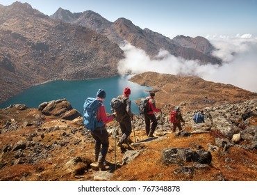 Group of tourists with backpacks descends down mountain trail to lake during a hike in the national park Lantang, Nepal.Beautiful inspirational landscape, trekking and activity.
