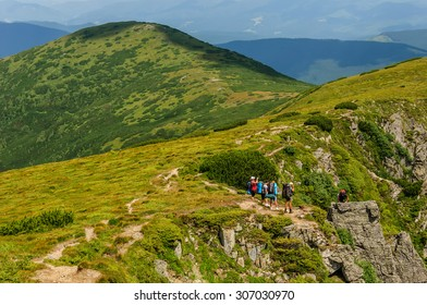 A group of tourists with big backpacks makes the ascent Hoverla in a thunderstorm