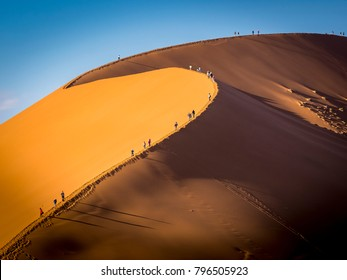 Group of tourists climbing a big dune at sunrise casting shadows in the sand, Namibia - Shutterstock ID 796505923