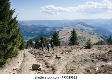 A group of tourists descends the mountain slope against the background of mountain peaks