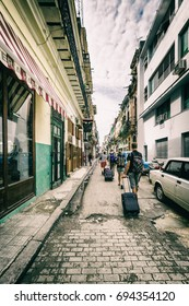 A group of tourists dragging their suitcases down a shabby street in Old Havana, Cuba. July 2017.