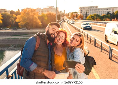 Group of tourists enjoying on vacation, young friends having fun walking on city street and making selfie during sunset.