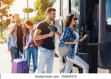 A group of tourists enters the bus. The guy and the girl are ready to sit down. They will travel on a modern black bus. Behind them is a group of tourists with luggage.