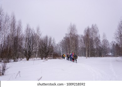 A group of tourists enters the forest on the edge of the village on a wintery overcast day.