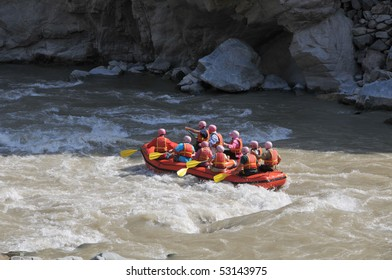 Group of tourists fighting with strong stream of mountain river.