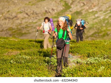 Group of tourists goes with backpacks and sticks up the mountain. Winning reaching life goal, success, freedom and happiness, achievement in mountains. Bright sunlight, sunset.