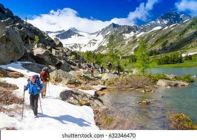 Group of tourists goes with backpacks and sticks up the stone mountain. Winning reaching life goal, success, freedom and happiness, achievement in mountains. Lake, snowfields, mountains, glacier.