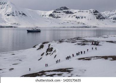 group of tourists at hike at svalbard island - Spitzbergen with cruise ship in the background